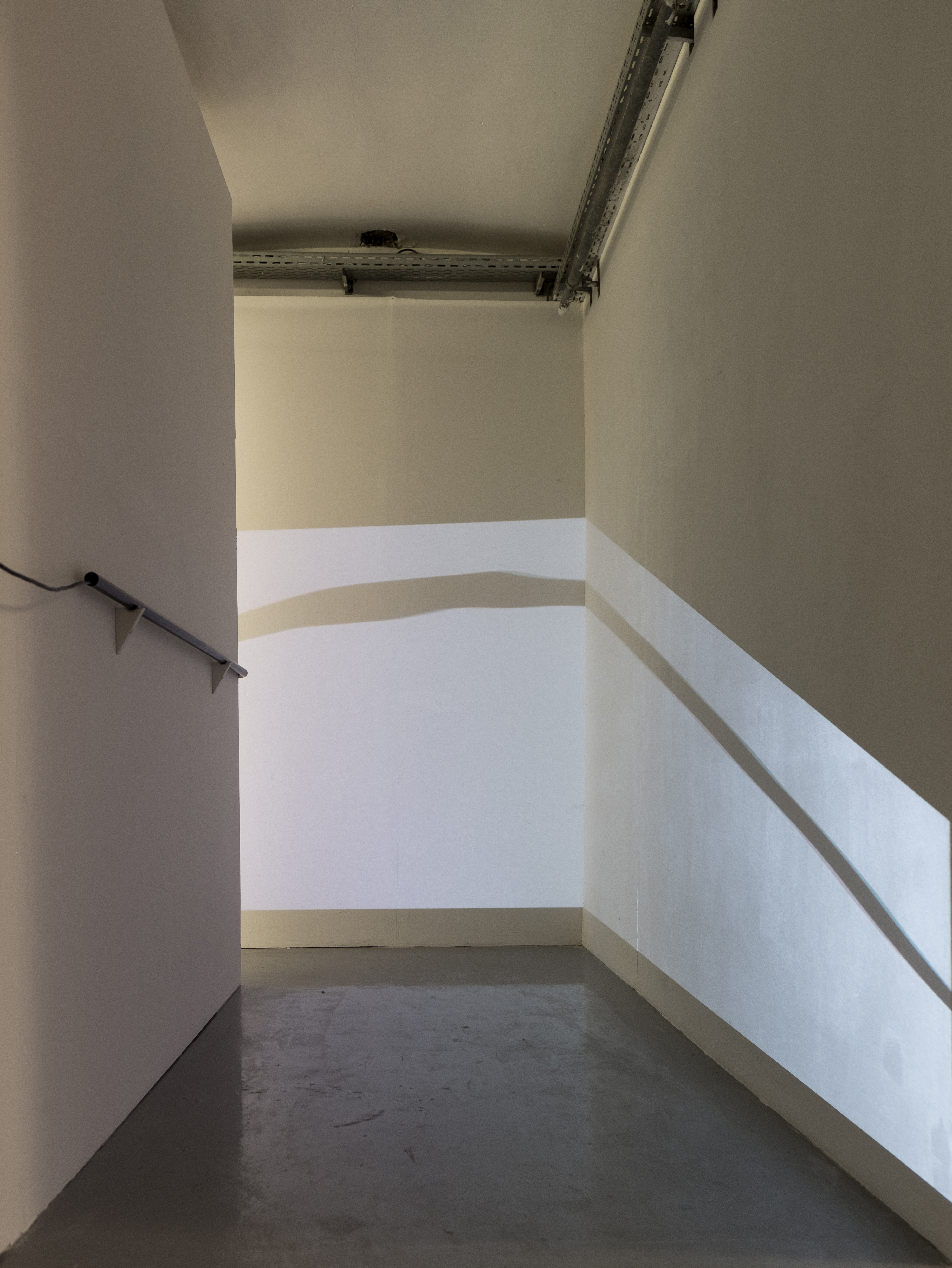 """Installationview of corridor connecting Room #1 and Room #2. Projection in Corridor showing: """"INKD"""" 16mm transferred to HD, 7min Loop, silent, videoprojection by Stephan Lugbauer"""